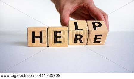 Help Is Here Symbol. Businessman Turns Cubes And Changes The Word Help To Here. Beautiful White Back