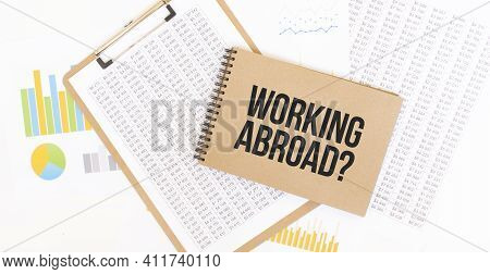 Text Working Abroad On Brown Paper Notepad On The Table With Diagram. Business Concept