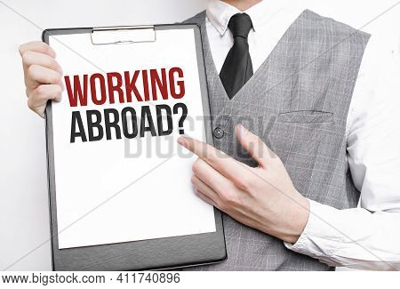 Working Abroad Inscription On A Notebook In The Hands Of A Businessman On A Gray Background, A Man P