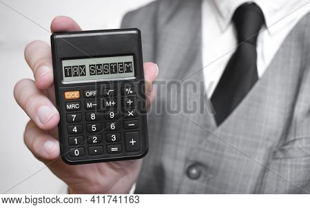 Tax System Word Text Inscription On Calculator In A Male Hand Of A Businessman In White Shirt And Bl
