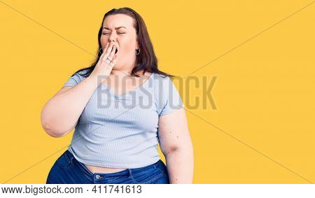 Young plus size woman wearing casual clothes bored yawning tired covering mouth with hand. restless and sleepiness.