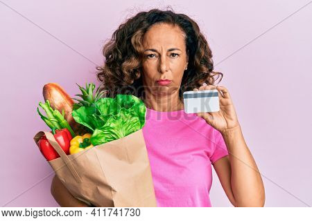Middle age hispanic woman holding groceries and credit card depressed and worry for distress, crying angry and afraid. sad expression.