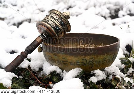 A Copper Tibetan Bowl And Prayer Wheel In The Snow. Translation Of Mantra Transform Your Impure Body