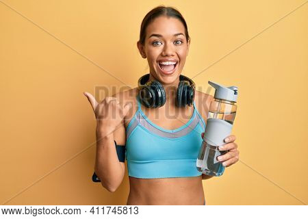 Beautiful hispanic woman wearing sportswear drinking bottle of water pointing thumb up to the side smiling happy with open mouth