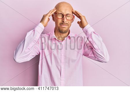 Bald man with beard wearing casual clothes and glasses with hand on head, headache because stress. suffering migraine.