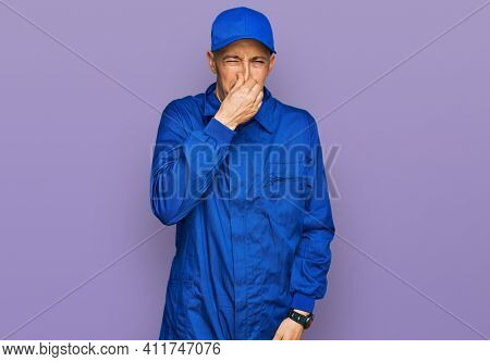 Bald man with beard wearing builder jumpsuit uniform smelling something stinky and disgusting, intolerable smell, holding breath with fingers on nose. bad smell