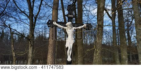Cross And Jesus Christ Statue On Forest Background. Religious Symbol. Catholicism And Christianity.m