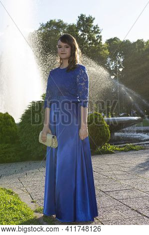 Cute Graduate Girl In Modern Dress Posing In The Park. Adorable Fashionable Female Model Relaxing Ou
