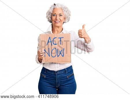 Senior grey-haired woman holding act now banner smiling happy and positive, thumb up doing excellent and approval sign