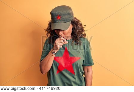 Middle age brunette woman wearing t-shirt and cap with red star symbol of communism feeling unwell and coughing as symptom for cold or bronchitis. Health care concept.