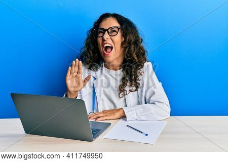 Beautiful middle age doctor woman doing video call waving to laptop angry and mad screaming frustrated and furious, shouting with anger looking up.
