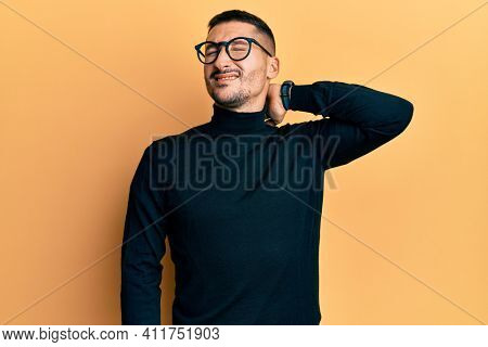 Handsome man with tattoos wearing turtleneck sweater and glasses suffering of neck ache injury, touching neck with hand, muscular pain