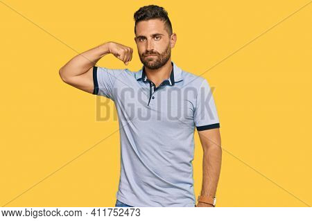 Handsome man with beard wearing casual clothes strong person showing arm muscle, confident and proud of power
