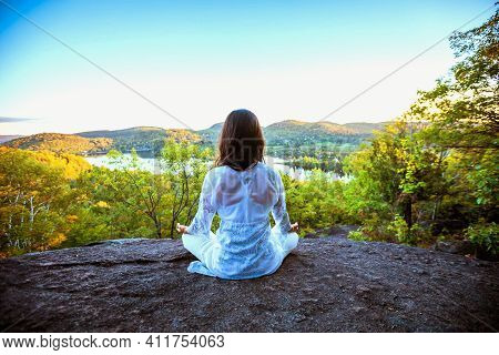 Rear View Of Woman Meditating On Cliff