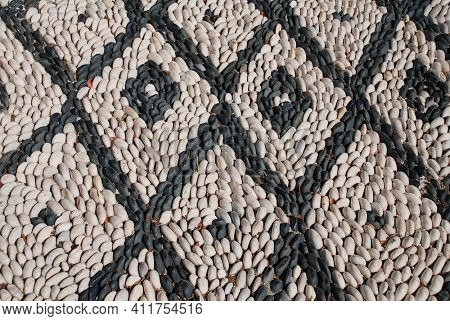 A black and white pebble mosaic on the Greek island of Symi. Made from sea pebbles Hoklakia mosaics are traditional to the Dodecanese islands.