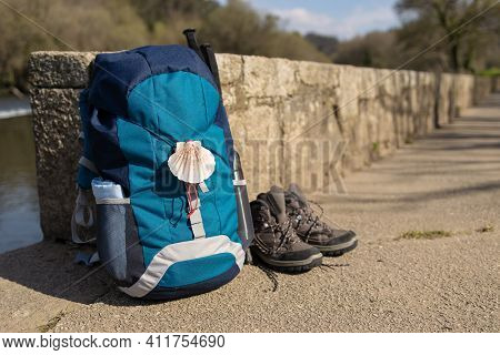 Backpack With Seashell Symbol Of Camino De Santiago, Trekking Boots And Poles Leaning On Stone Wall.