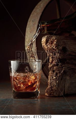 Whiskey Is Poured From A Bottle Into A Frozen Glass With Natural Ice. Rough Rusty Background.