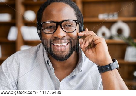 Webcam View Of Cheerful African American Young Businessman In A Headset Holding The Microphone, Atte
