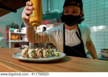 Professional Sushi Chef Wearing Protective Mask And Gloves Adding Sauce While Preparing Sushi Rolls