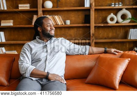 A Carefree And Cheerful African-american Guy Rests On The Sofa In Stylish Living Room, Bookshelves O