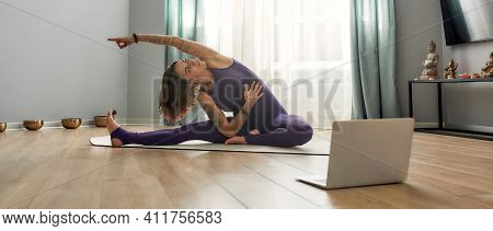 Young Girl Exercising At Home On A Sports Mat. Young Girl In Sportswear Siting On A Sports Mat And S
