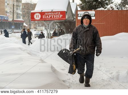 Lutsk, Ukraine - February 12,2020: City Street After Blizzard. An Elderly Man With Snow Shovel In Wi