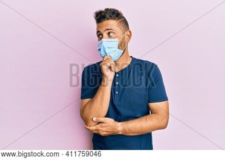 Handsome man with beard wearing medical mask thinking concentrated about doubt with finger on chin and looking up wondering