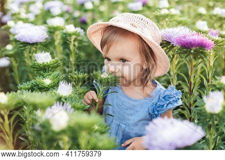 Girl In Flower Fields, Outdoor Portrait. Little Toddler Lovely Girl With Flowers At Beautiful Garden