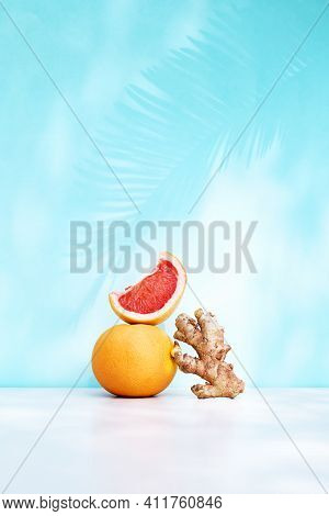 Fresh Healthy Grapefruit And Ginger On Sunlight With Shadows. Minimal Food Creative Balance Concept