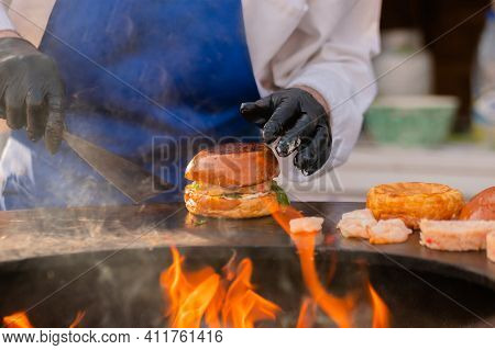 Chef Preparing Burgers With Shrimp, Prawn And Fish Cutlet On Brazier With Hot Flame At Summer Local