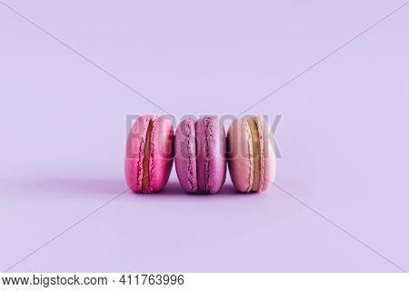 Tasty French Macarons On A Violet Pastel Background. Pink And Violet Macarons. Place For Text.