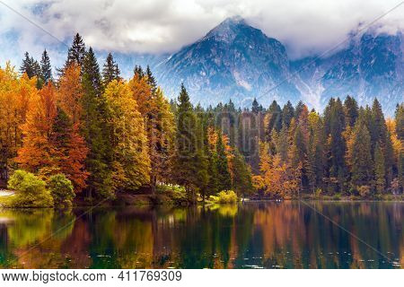 Lake Fuzine. Grand mountain range Dolomite Alps in thunderclouds. Autumn in Northern Italy. Orange, yellow and red trees are reflected in the green smooth water of the lake.