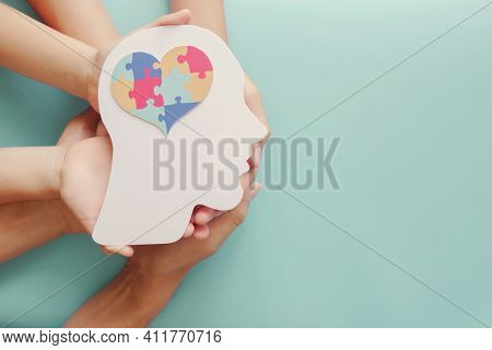 Adult And Chiildren Hands Holding Head With Jigsaw Puzzle Heart Shape, Autism Awareness,autism Spect