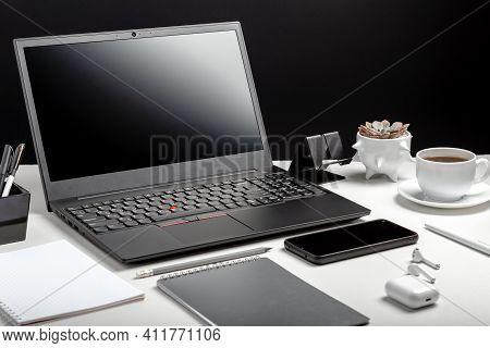 Modern Workplace. Desktop With Laptop Pc Smart Phone, Office Suppliers, Coffee Cup Plant Flower Head