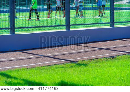 public stadium for sports - team of soccer players on a football field, running track closeup and green grass