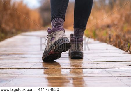 Girl's Feet Walking On Wooden Boardwalk With Hiking Boots On Rainy Day