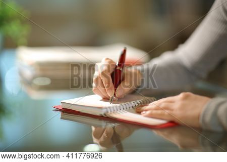 Close Up Of A Woman Hands Writing On Paper Agenda In The Night At Home