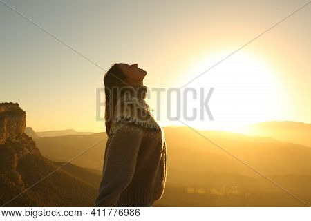 Profile Of A Woman Breathing Fresh Air In Nature At Sunrise In A Warm Winter