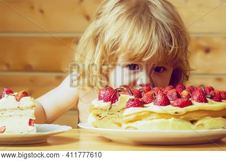 Funny Child Baby Eating Tasty Creamy Pie Or Cake With Red Strawberry