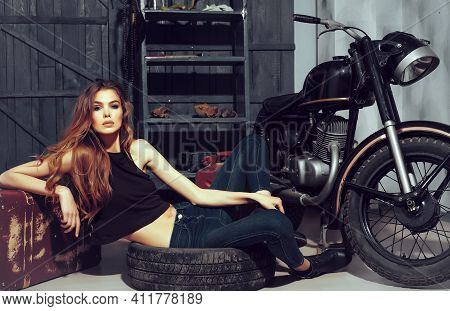 Sexy Woman Model In Erotic Leather Jacket Lying In Dirty, Rubber Tire On Floor On Motorcycle Garage