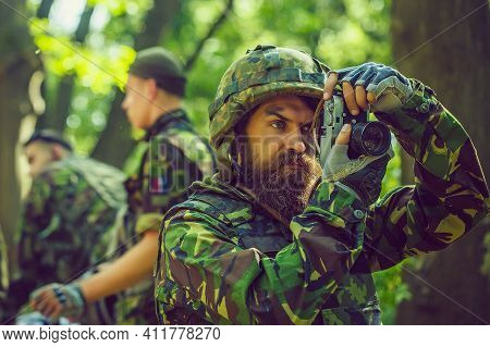 Soldier Man Reporter With Serious Face In Ammunition And Helmet Holding Camera In His Hands On Backg