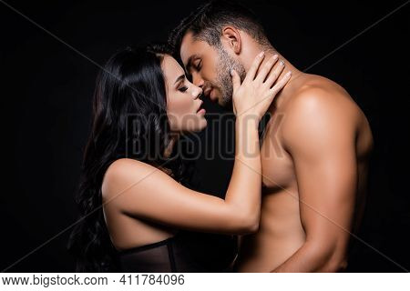 Side View Of Woman Kissing Shirtless Boyfriend Isolated On Black.