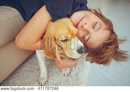 Happy Boy And Dog Beagle Hugs Her With Tenderness, Smiles, Looks At The Camera At Home. Pets. Emotio