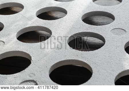 Abstract Geometric Composition With Shadows. A Sheet Of White Styrofoam With Round Holes Rests On To