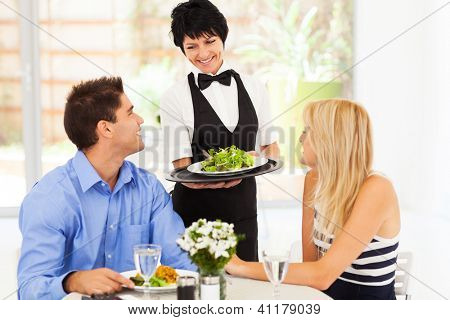 happy waitress serving customers in restaurant