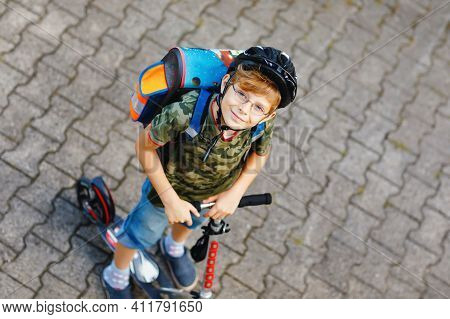 Active School Kid Boy In Safety Helmet Riding With His Scooter In The City. Happy Child In Colorful