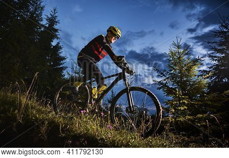 Smiling Young Man In Sports Cycling Suit Riding Bicycle Downhill With Beautiful Blue Sky On Backgrou