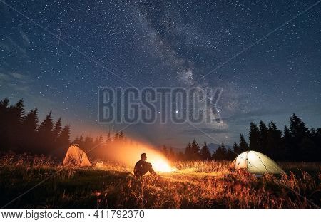 Silhouette Of Male Traveler Sitting Near Campfire And Camp Tent Under Beautiful Night Sky With Stars