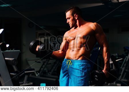 Shirtless Strong Bodybuilder Training Biceps In Gym. Dumbbells Exercises. Sportsman With Shirtless T