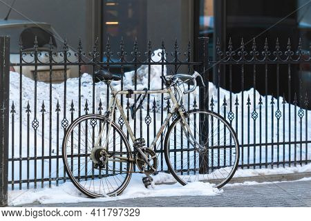 Riga, Latvia - February 17, 2021: Sport Bicycle Are Parked And Locked To A Fence On The Sidewalk In